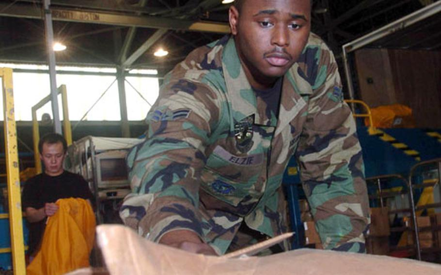 Airman 1st Class Jonathon Elzie from Detachment 2, Air Postal Squadron at Yokota Air Base, Japan, inspects a package Tuesday at the mail processing facility to ensure that it has proper markings before shipment.