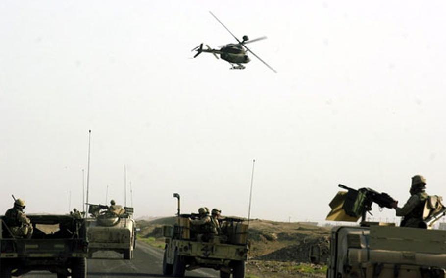 A Kiowa helicopter flies in low over Humvee guntrucks just outside Sabi Abor, Iraq.