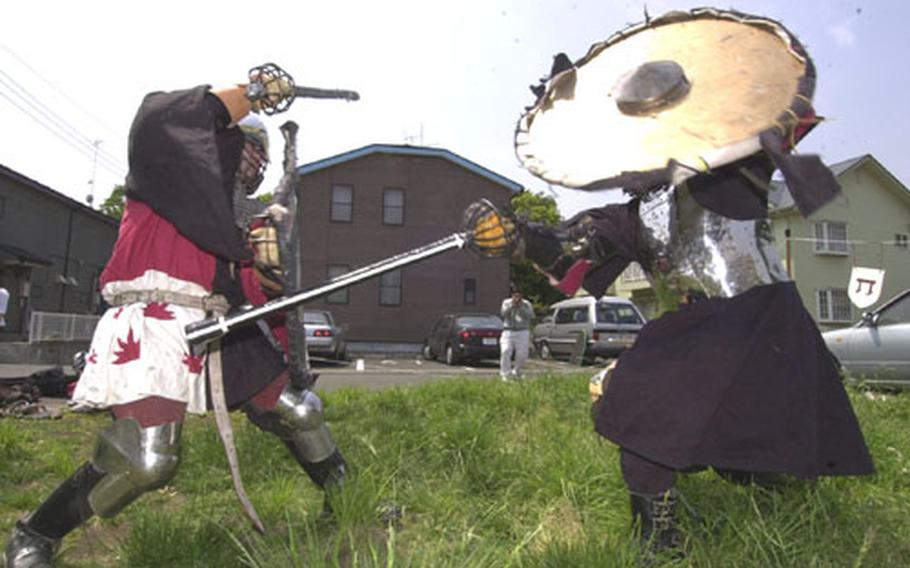 """Mark Iacampo, on the left, as """"Lord Codogan,"""" duels in a medieval combat with rattan swords against Yuji Okada as """"Lord Raven."""""""