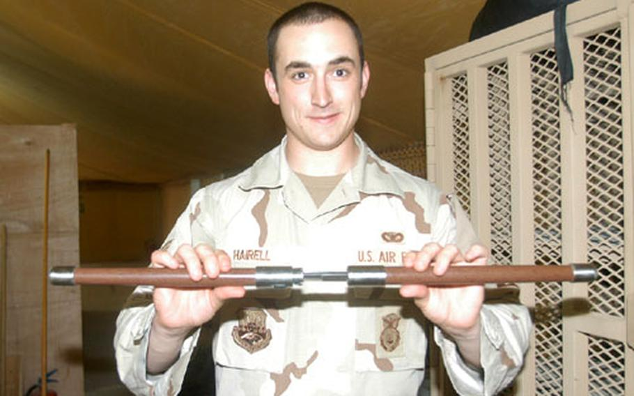 Senior Airman Andrew Hairell, a customs border clearing agent at the amnesty point on Camp Wolverine, displays a baton that separates into two swords. Swords are considered contraband. All servicemembers leaving from a deployment through Camp Wolverine are completely inspected for illegal items prior to departure.