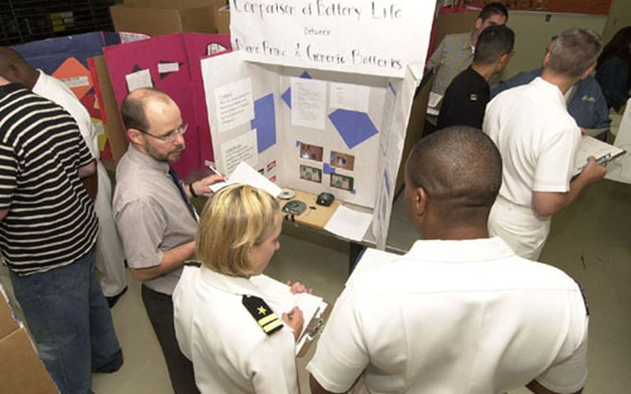 Educational Technology instructor, Gary Starrine (left), Lt. Rachel Spollen (center), and Petty Officer 1st Class Byron Stipe (right), from the Naval Pacific Meteorology and Oceanography Center judge a science project on the Comparison of Battery Life at Nile C. Kinnick High School Science Fair at Yokosuka Naval Base Friday.