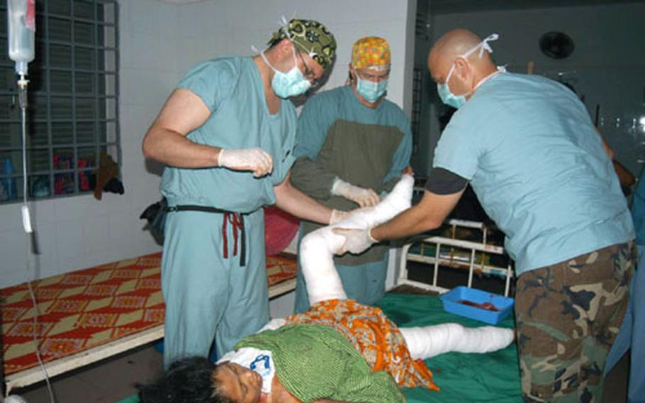U.S. Air Force Capt. Jason Rosenberg, left, Lt. Col. Jim Walter, center, and Master Sgt. Kristopher Krenzke bandage the legs of a Cambodian burn patient Thursday during the BRAVA 2004 medical mission to Kep, Cambodia.