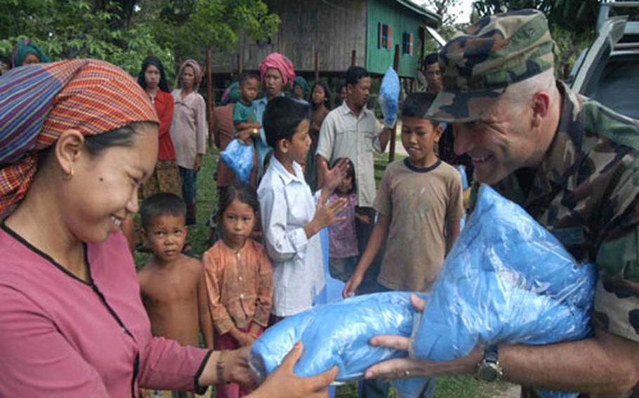 Air Force Tech. Sgt. Bryan Gray hands out mosquito nets to a Cambodian woman in a small village near Kep, Cambodia, Thursday. Gray is a biomedical equipment repair technician with the 18th Medical Support Squadron at Kadena Air Base, Okinawa. He's part of a 20-member team participating in BRAVA 2004.
