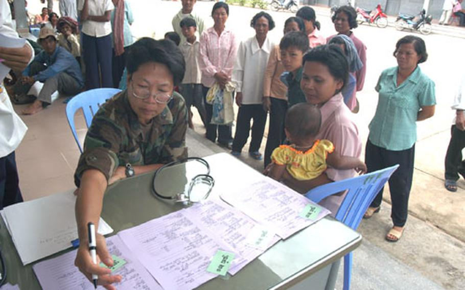 U.S. Air Force Lt. Col. Diep Duong looks over a patient's screening paperwork as she assesses possible patients in a hospital compound in Kep. Duong is a nurse normally assigned to Det. 2, 13th Air Force International Health Specialist Program at Hickam AFB, Hawaii.
