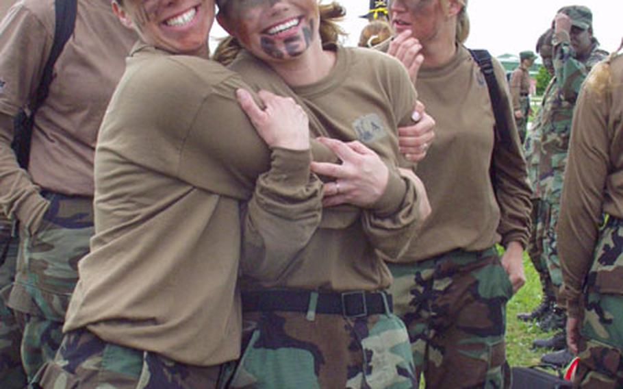 Julie Murray, left, and Adrianne Thrailkill, members of the Homefront Honeys team from the 1/4 Cavalry's Troop A, grab a hug while surrounded by teammates during a break in Saturday's Ladies Spur Ride. The event, for wives of soldiers in the 1/4 Cavalry and other 1st Infantry Division units based in Schweinfurt, Germany, was a scaled-down version of the daylong test of soldiering skills through which cavalry troopers earn their spurs.