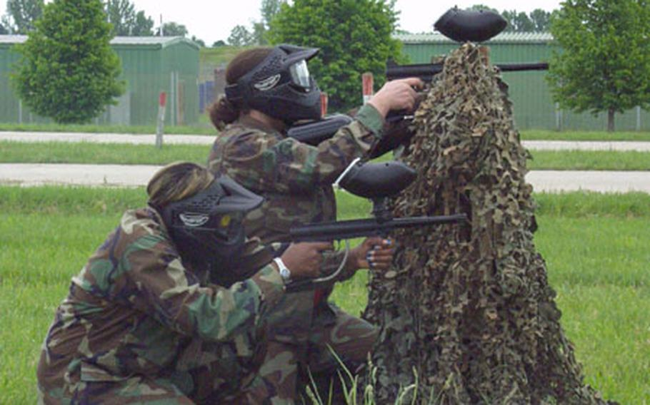 Cassandra Stith, foreground, and Jennifer Ratliff of the 1/4 Cavalry's headquarters troop team Victory Ladies crouch behind a barricade on the paintball-assault course during Saturday's Ladies Spur Ride at Conn Barracks in Schweinfurt, Germany.