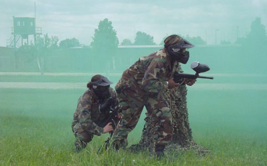 Jennifer Ratliff, left, and Cassandra Stith of the 1/4 Cavalry's headquarters troop team Victory Ladies prepare to advance under a cover of smoke during Saturday's Ladies Spur Ride at Conn Barracks in Schweinfurt, Germany.