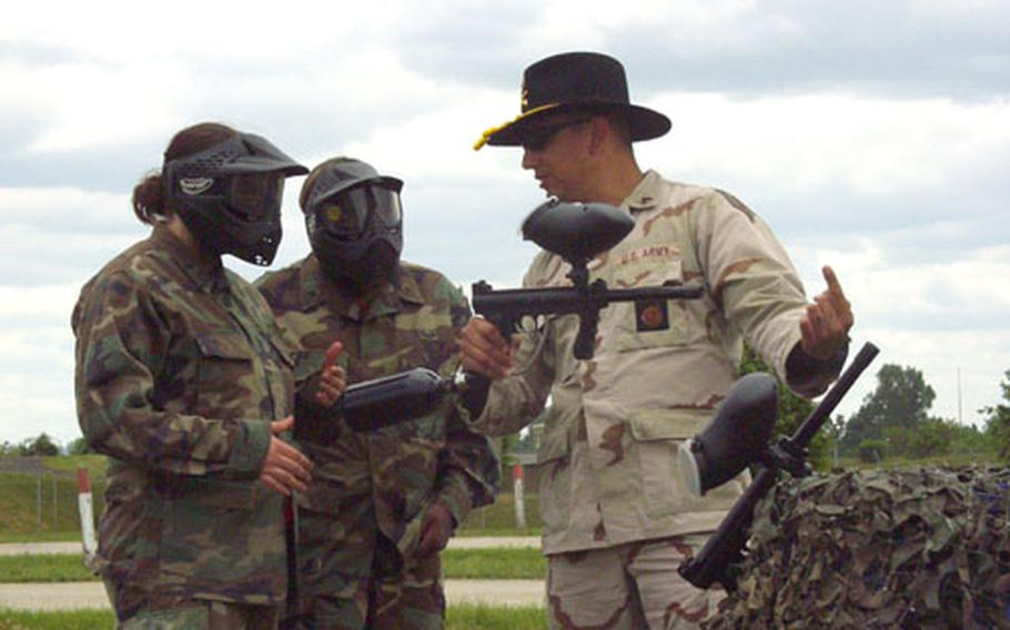 Sgt. Thomas Dever gives Jennifer Ratliff, left, and Cassandra Stith some last-minute advice on firing their paintball-assault rifles during Saturday's Ladies Spur Ride om Schweinfurt, Germany. Ratliff, Stith and 142 other wives of soldiers from the 1/4 Cavalry as well as from other Schweinfurt-based 1st Infantry Division units earned their cavalry spurs by performing basic soldier skills in teams at Schweinfurt's Conn Barracks.