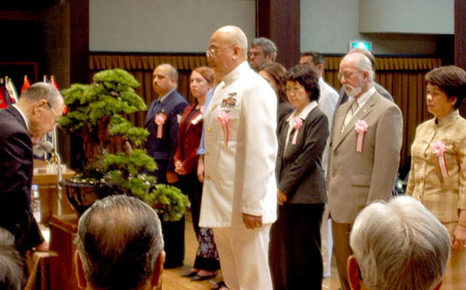 """Master Chief Petty Officer Nolly Dizon steps up to receive a certificate as a representative of all non-Japanese awardees during the 54th Zenkokai """"Good Conduct"""" Award ceremony Saturday at Meiji Shrine in Tokyo."""