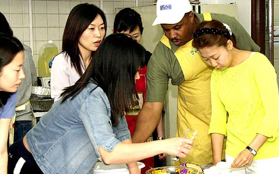 Marvin Sanders, center, walks a group of new brides through the cooking portion of the USO's Cross-Cultural School at Camp Kim, South Korea.