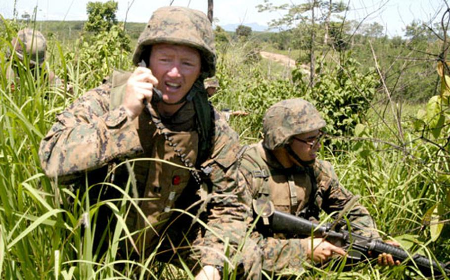 Marine engineer platoon commander Capt. Garry McCullar, left, issues orders over a radio during a double breach as part of the Cobra Gold exercise in Thailand.