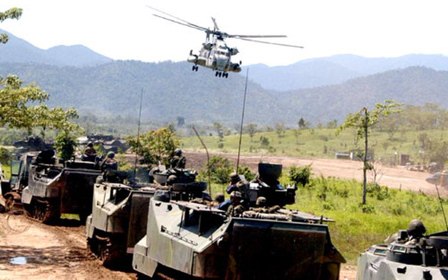 """Marines wait to attack """"enemy"""" positions in Amphibious Assault Vehicles (AAVs) while a helicopter hovers overhead as part of the Cobra Gold exercise in Thailand."""