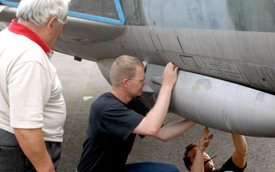 Giovanni Follador, who runs an air museum in Pordenone, watches as Capt. Ed Eisenhauer, left, and 1st Lt. Andrew Wojtalewicz try to take off a panel of the Hawker Hunter fighter jet that will soon grace Follador's museum.