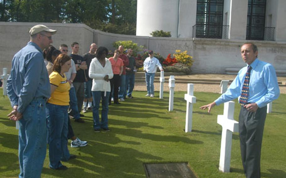 Arthur Brooks, right, a staff member at the American Military Cemetery at Madingley, England, explains the story of the cemetery Thursday to about 25 staff sergeants from the Professional Development Center at RAF Mildenhall, England.