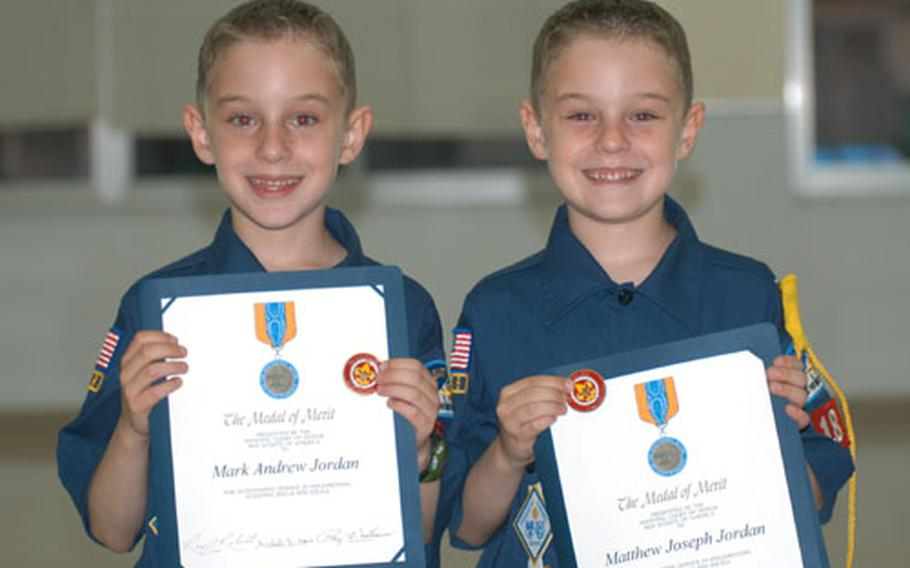 Mark Jordan, left, and twin brother Matthew Jordan received the Medal of Merit from the Boy Scouts of America Tuesday for saving the life of 8-year-old Nicky Cullen last year at Misawa Air Base, Japan.