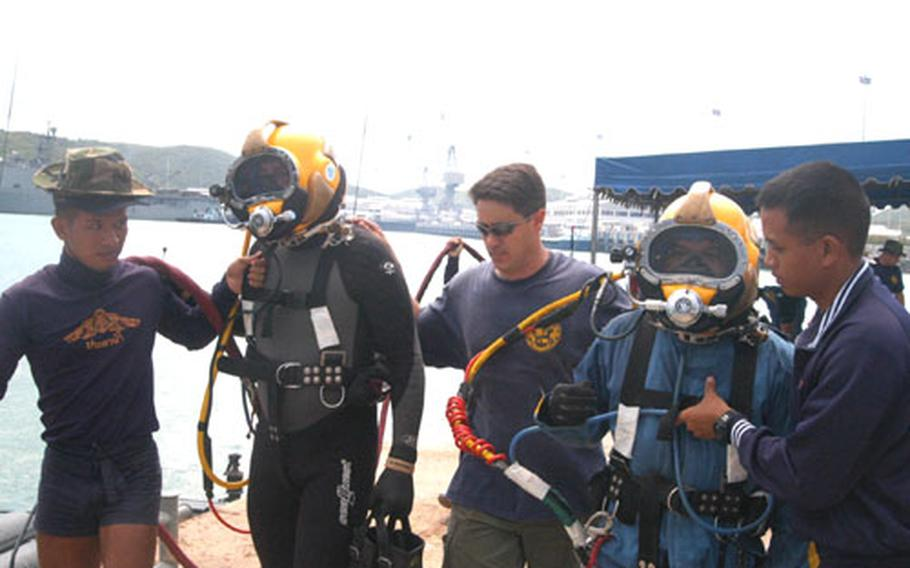 U.S. Navy divers prepare to enter the water with a Thai diver at Sattahip Naval Base, Thailand.