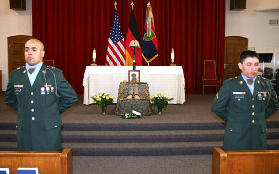 Pfc. Daniel Medeles of Troop C, 1st Squadron, 4th Cavalry, left, and Pvt. Ronald Gonzalez, Headquarters and Headquarters Troop, 1st Squadron, 4th Cavalry, stand before a memorial display for Spc. Michael Campbell in Schweinfurt, Germany, on Wednesday.