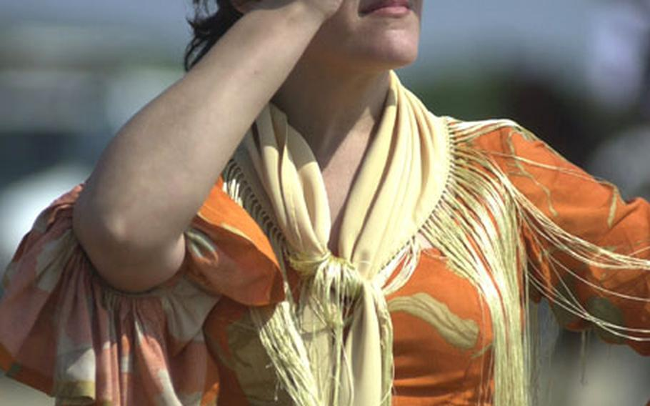 A Spanish woman in a traditional gypsy dress on Wednesday watches horses and carts unload from a ferry boat onto the coast of Donana National Park near Sanlúcar de Barrameda, Spain. More than 1 million people are expected to make the pilgrimage to the city of El Rocío this week. It is Spain's largest Catholic pilgrimage.
