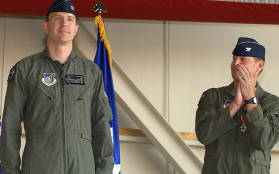Air Force Col. William W. Uhle Jr., left, is prsented as new commander of the 8th Fighter Wing at Kunsan Air Base during ceremony there Thursday morning. At right of photo is Col. Robin Rand, who until Thursday commanded the wing for the past year.