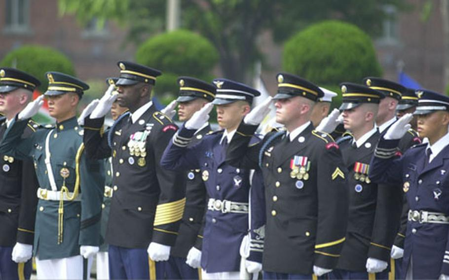 Members of an honor guard salute as taps is played during a Yongsan Garrison repatriation ceremony Thursday. Eighteen sets of remains thought to be those of American soldiers killed in the Korean War were honored.