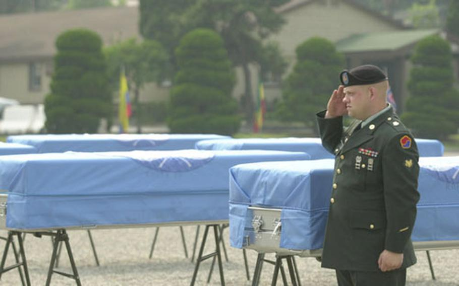 Before a repatriation ceremony Thursday at Yongsan Garrison, a lone American soldier stands and salutes in front of metal coffins carrying remains thought to be those of U.S. soldiers killed in the Korean War.