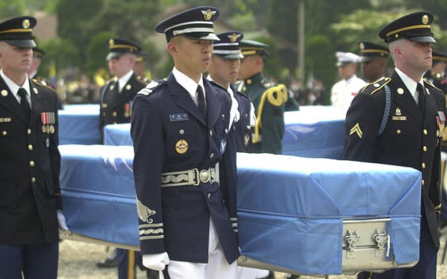 An honor guard carries a casket containing remains thought to be those of an American soldier killed during the Korean War. Eighteen sets of remains were repatriated Thursday at a Yongsan Garrison ceremony.