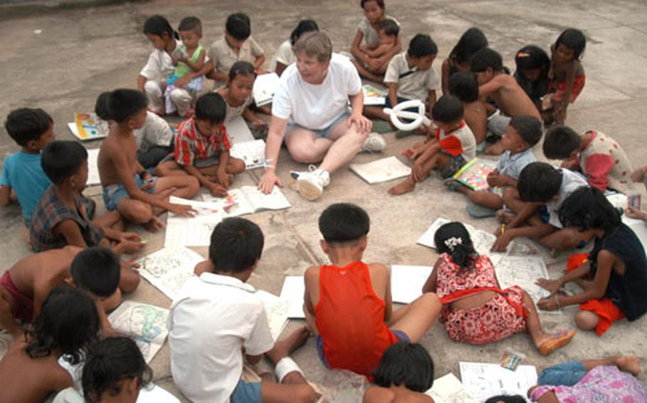 Air Force Master Sgt. Rita Greiner leads a coloring book session with Cambodian children in a hospital compound in Kep. Sergeant Greiner is an orthopedics technician on a 20-member blast resuscitation and victim assistance mission - also known by medics as BRAVA - sponsored by the U.S. military's Pacific Command.