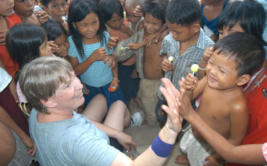 Air Force Master Sgt. Rita Greiner gives a high five after handing out a lollipop to a Cambodian boy as a pack of Cambodian children she's become a surrogate mother to gather around in a hospital compound in Kep.