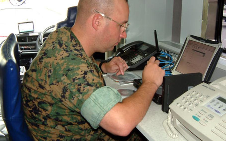 Marine Staff Sgt. Michael Abballe programs a new computer at a workstation in the Marines' new $450,000 mobile comand post on Camp Foster. The vehicle is one of two purchased for Marine bases in Japan. Thirteen others are being provided for Marine bases in the U.S.