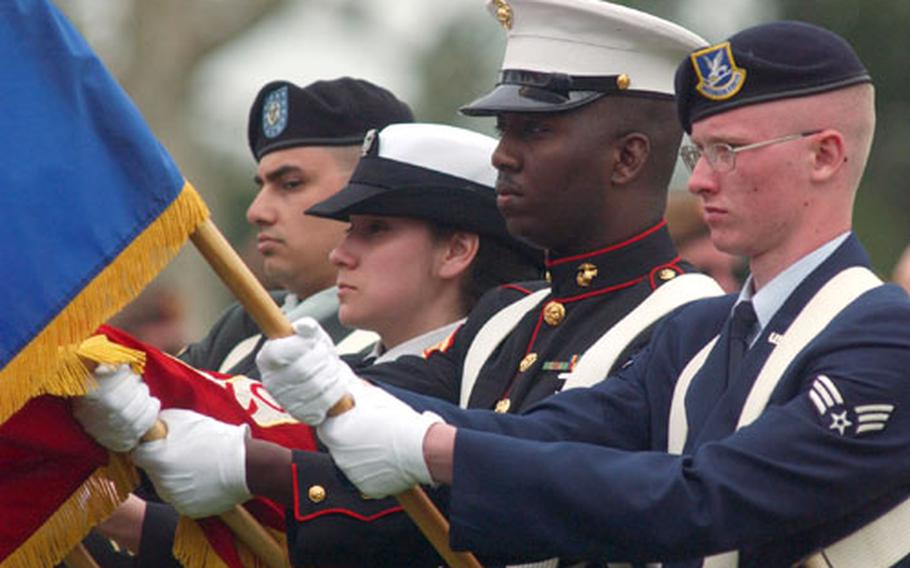 From left, Army Sgt. Fabian Montoya, Yeoman 2nd Class Clorinda Morrison, Marine Sgt. Marwin Glenn and Senior Airman Eric Ackerstrom present the service flags during a Memorial Day ceremony at the Netherlands American Cemetery and Memorial in Margraten, Netherlands, on Sunday.