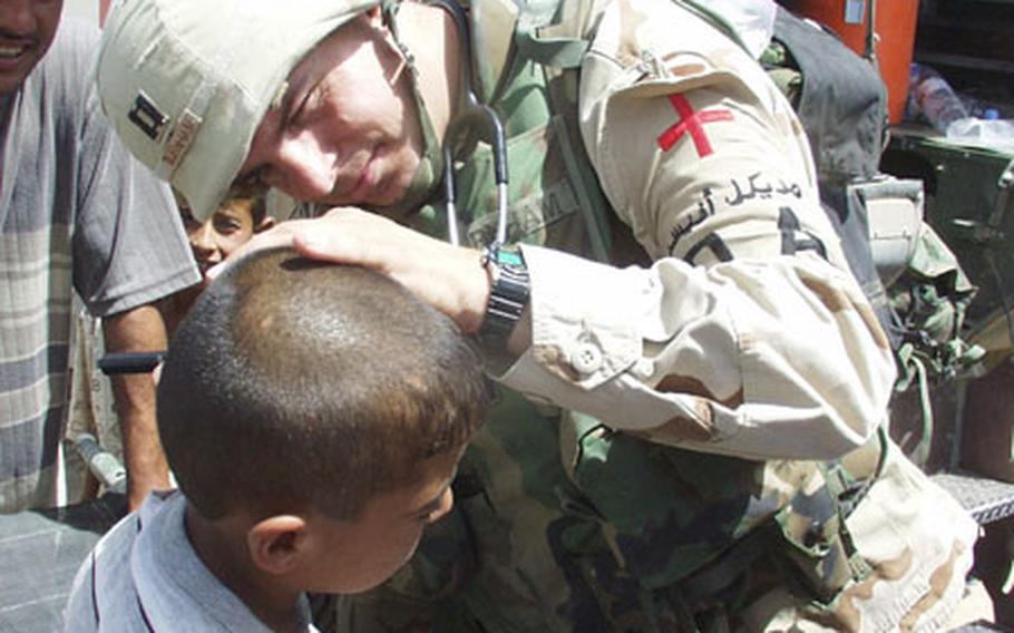 Capt. Kevin Burnham, a physician's assistant with the 2/7 Cavalry Regiment, examines an Iraqi boy's ear during a goodwill visit Friday to Mushada, Iraq, a village 30 miles north of Baghdad.