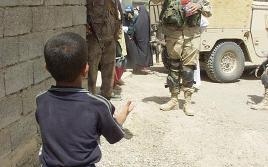 An Iraqi boy plays catch with 2nd Lt. Francis McCahill of Melbourne, Fla., a medical platoon leader with the 2-7 Cavalry Headquarters Headquarters Company during a trip to Mushada, Iraq, to provide medical checkups and medicine to residents.