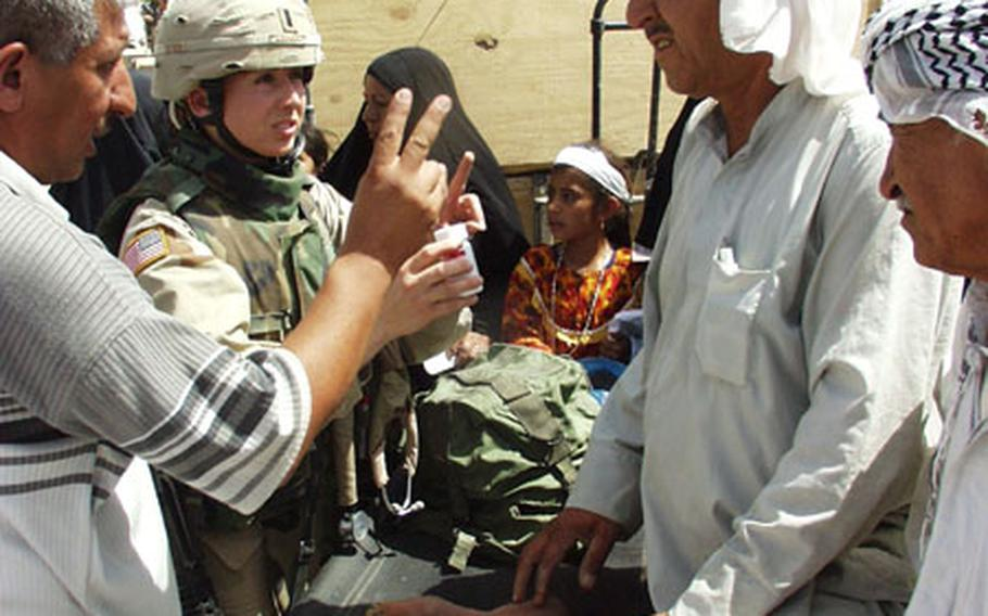 First Lt. Robin Lowery of Little Rock, Ark., a physician's assistant with Company, 39th Medical Group, tells a man through an interpreter about his medical treatment during a visit Saturday to Mushada, Iraq. Lowery was part of an Army convoy that made a goodwill trip to the small village located about 30 miles north of Baghdad.