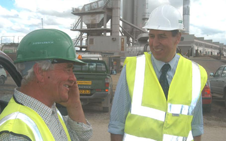 Neil Smith, left, general foreman, and Tim Eden, project manager, chat Friday about the runway reconstruction project at RAF Mildenhall, England, in the shadow of a temporary plant built to mix the tons of concrete needed for the project.