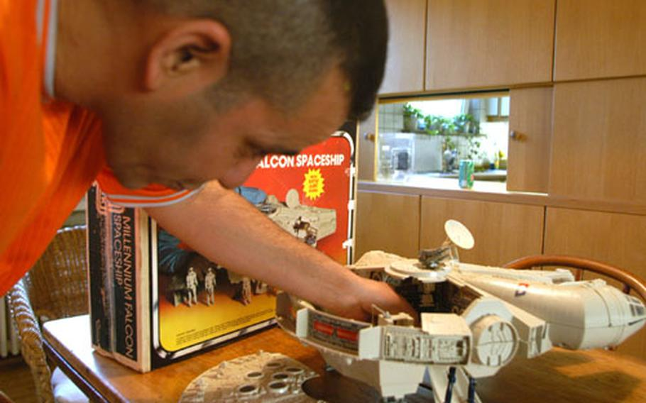 """Staff Sgt. Luis Olmo-Jimenez, a corrections officer with the 9th Military Police Detachment in Mannheim, Germany, shows off a toy spaceship that is part of his """"Star Wars"""" collection."""