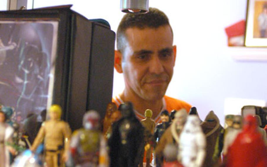 """Staff Sgt. Luis Olmo-Jimenez, a corrections officer with the 9th Military Police Detachment in Mannheim, Germany, shows off some of the """"Star Wars"""" figures that he's collected over the years."""