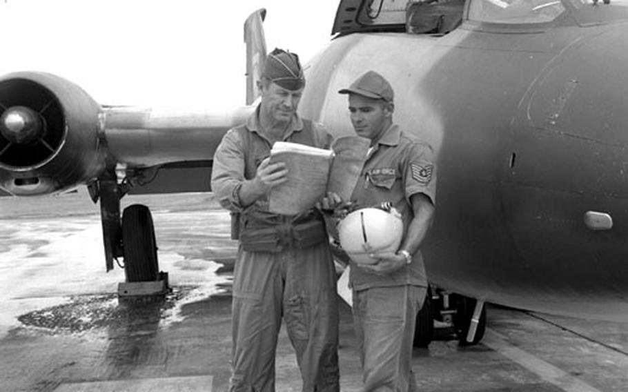 Col. Chuck Yeager and crew chief TSgt. Rodney T.J. Sirois, beside a B-57 aircraft.
