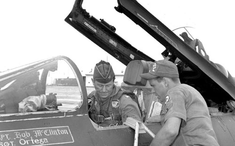 F-100 crew chief Airman 2nd Class James Rohl helps Col. Yeager settle into the cockpit.