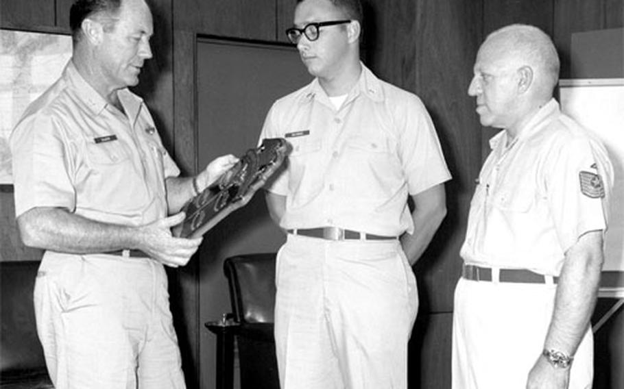 On a more down-to-earth matter, Col. Chuck Yeager presents a plaque for outstanding performance to 2nd Lt. Thomas Holycross, center, and MSgt. Richard M. Rochlin, right.