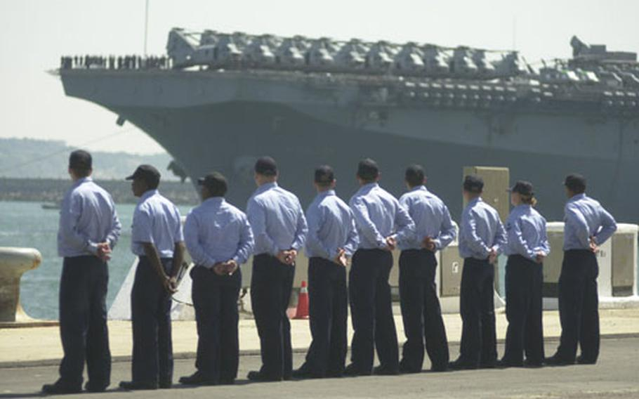 Sailors wait for the amphibious assault ship USS Wasp to pull into Naval Station Rota, Spain's port on Tuesday.