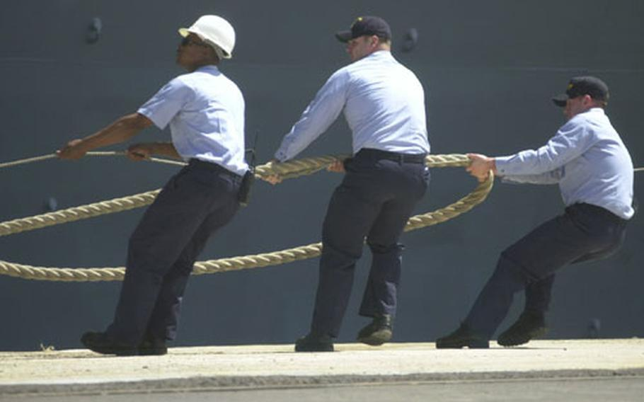 Sailors pull the lines to help moor the amphibious assault ship USS Wasp at Naval Station Rota, Spain, on Tuesday.