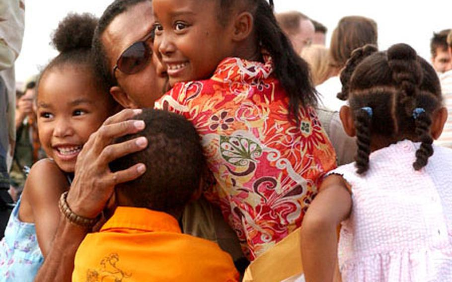 A senior airman returning home from deployment is greeted by his four children during a welcoming ceremony at Yokota Air Base.