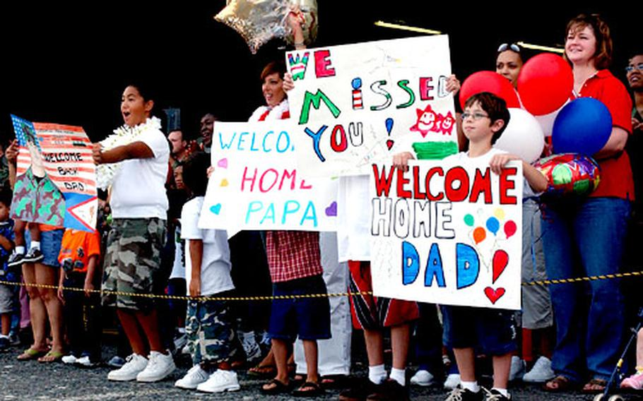 Yokota Air Base family members and co-workers cheer for the 90 airmen returning from deployment.