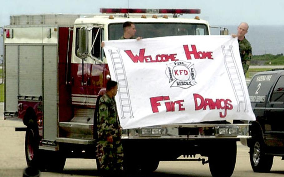 Kadena Air Base fire personnel hold up a sign welcoming home some of their comrades from deployment. They also lined up several trucks and flashed the lights and blew horns and sirens.