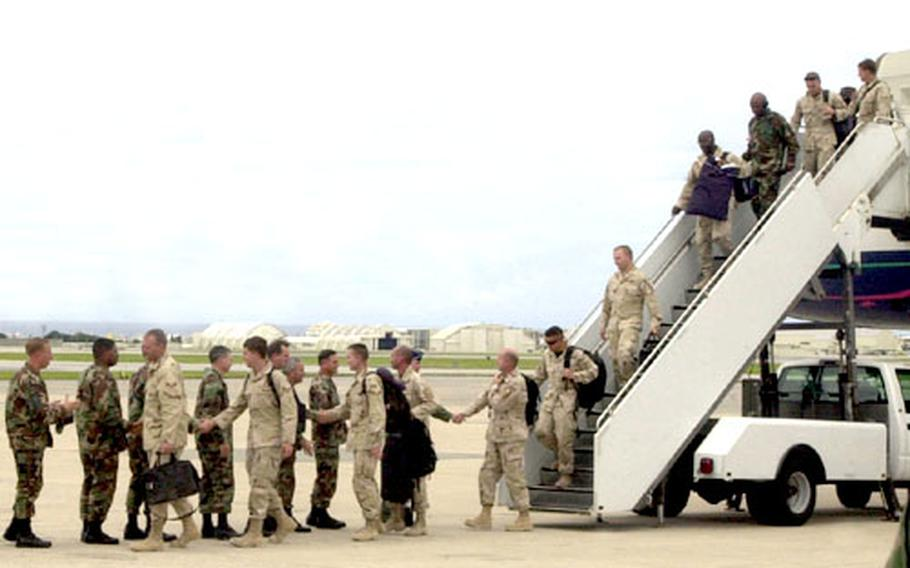 Servicemembers leave the plane at Kadena on their way back from deployment.