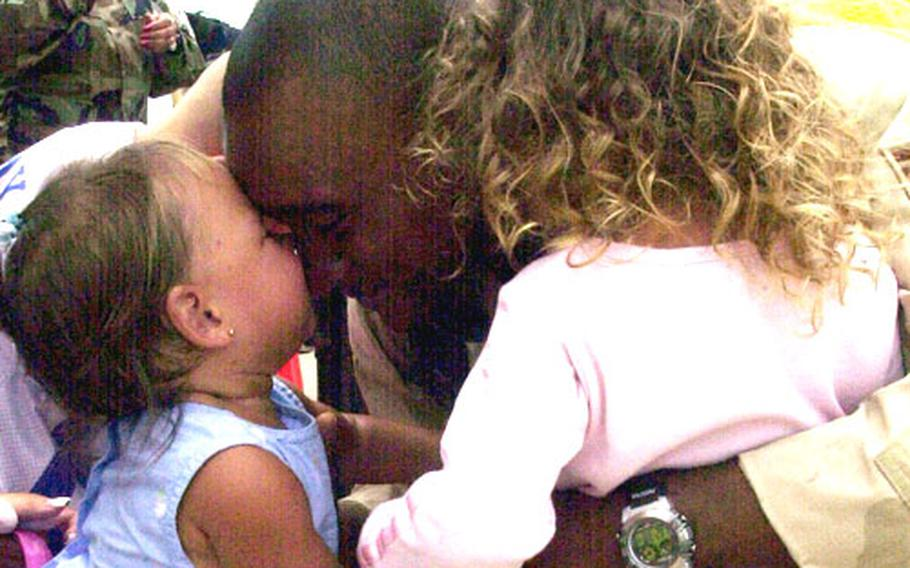 Air Force Staff Sgt. Corey Coleman, a firefighter with the Kadena Air Base's 18th Civil Engineer Squadron, gets a kiss on the nose from 1-year-old daughter Gabrielle as he hugs 3-year-old Alexis.