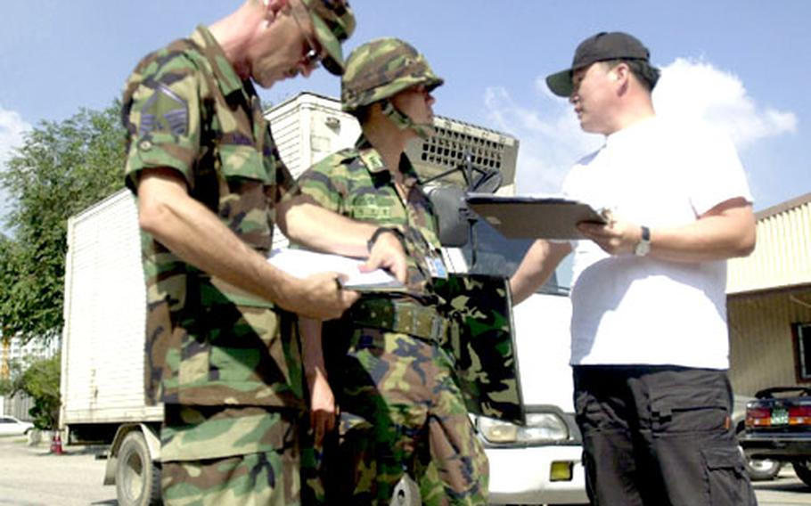 Air Force Master Sgt. Andy Davis, left, of Special Operations Command Korea, finishes paperwork during an exercise to test the transition of civilian assets into military use. A South Korean soldier and private contractor look on.