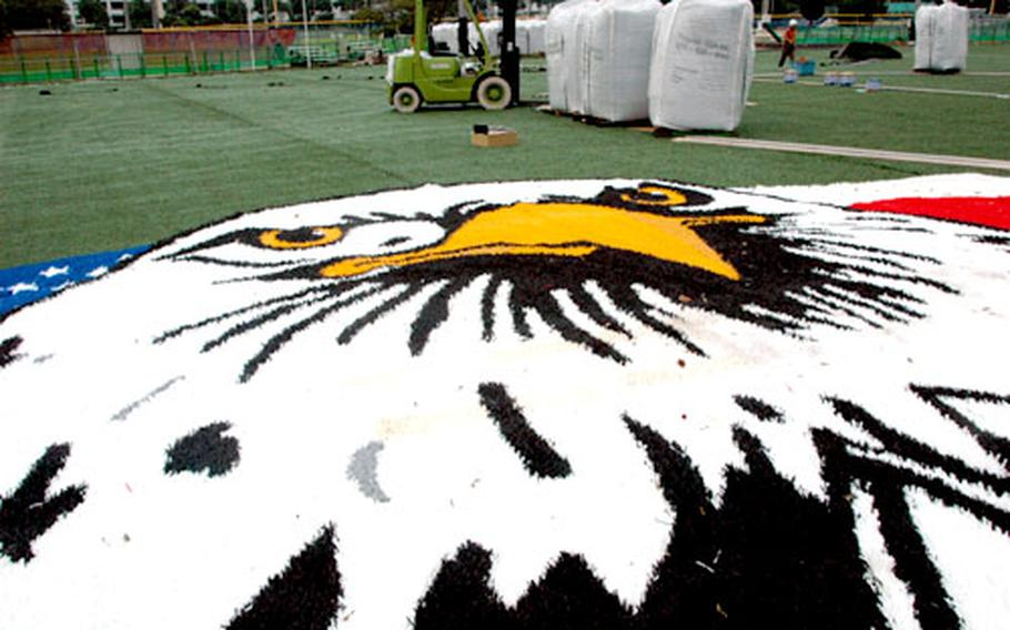 The Morale, Welfare and Recreation Sports logo will soon be installed in the center of the new field. The logo is made from the same type of artificial grass as the rest of the field, but produced according to a programmed pattern of colors. It will never need to be touched up with paint or colored chalk.