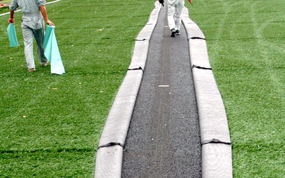Japanese workers carefully peel back strips of green artificial turf that will later be replaced by white turf that serves as the soccer field boundaries. The field will also have yellow lines for flag football.