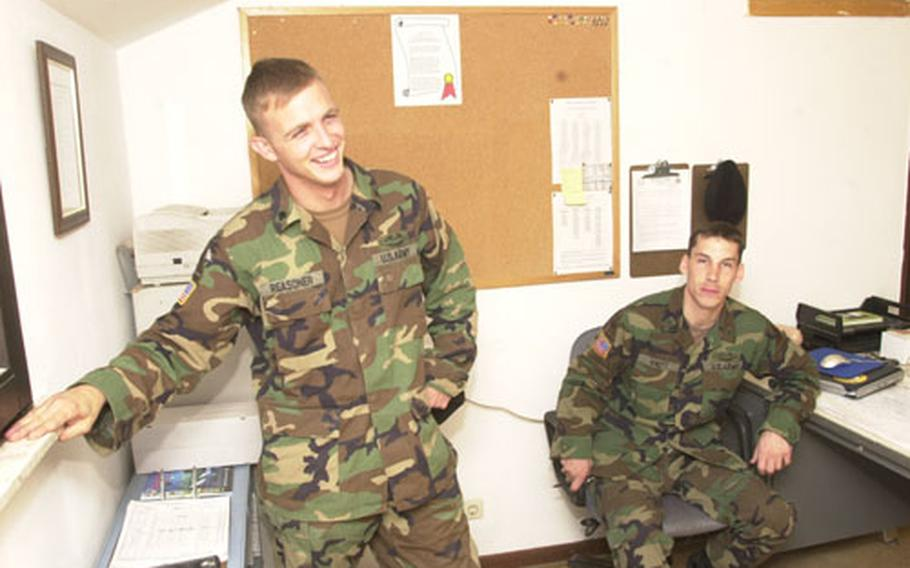Spc. Joshua Reasoner, left, and Staff Sgt. Eric Knott talk about their time at war while relaxing at Knott's office at battalion headquarters.